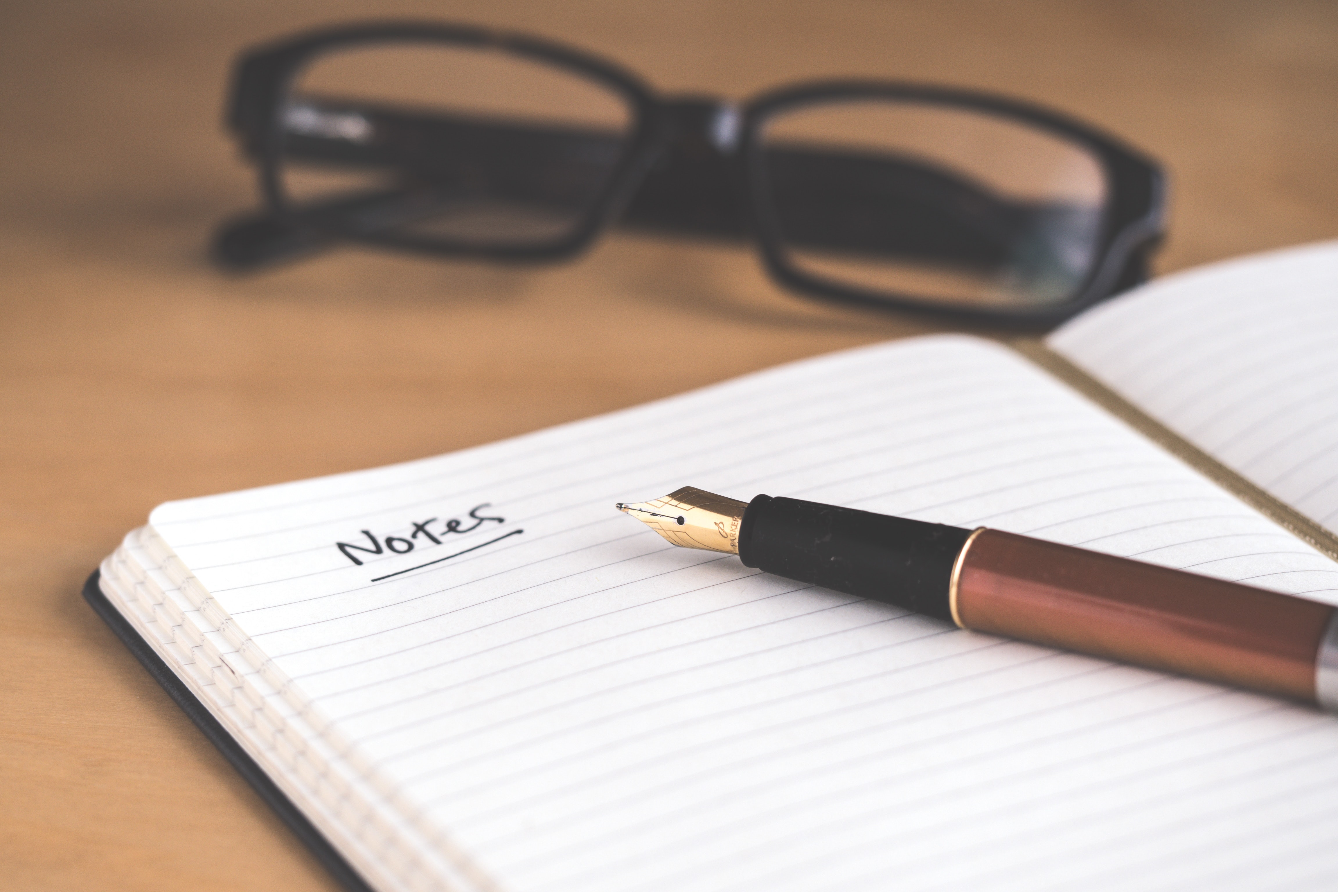 """A traditional notebook on a desk with the word """"notes"""" at the top of the page"""